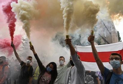 Membros da diáspora bielorrussa e ativistas ucranianos queimam granadas de fumaça brancas e vermelhas durante um comício em apoio ao povo bielorrusso que protestava contra fraude eleitoral, em frente à embaixada bielorrussa em Kiev em 13 de agosto de 2020. -  (foto: Sergei SUPINSKY / AFP)