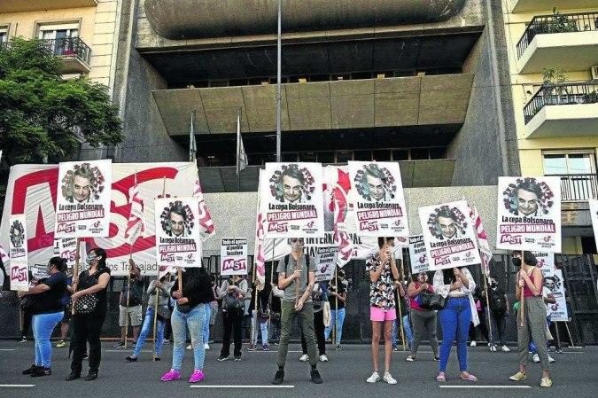 Manifestantes exibem cartazes com os dizeres