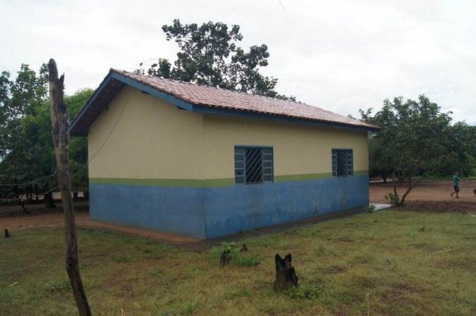 A escola está cercada por árvores. É uma construção com duas janelas e está pintada de amarelo com azul e uma listra verde entre as cores.