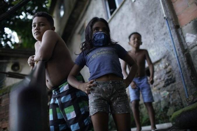 Na foto, crianças assistem desinfecção no Rio de Janeiro para conter a covid-19. Maior parte das escolas públicas no país está fechada desde o início da pandemia - (crédito: Mauro Pimentel/AFP)