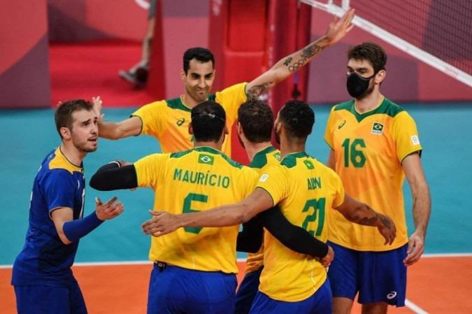 Atletas da seleção masculina de vôlei estão em uma quadra, se abraçando, comemorando um ponto; eles vestem camisa amarela e bermuda azul.