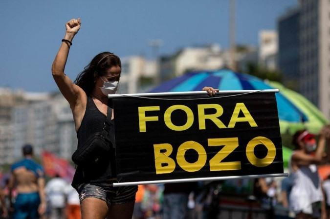 Pessoas participam de uma manifestação convocada por grupos de direita e partidos para exigir o impeachment do presidente Jair Bolsonaro, na praia de Copacabana, no Rio de Janeiro, Brasil, em 12 de setembro de 2021. - (crédito: DOUGLAS SHINEIDR / AFP)